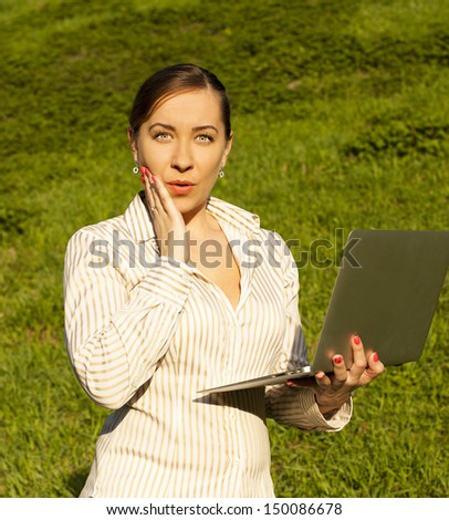 Business woman on the street with laptop. shock - stock photo