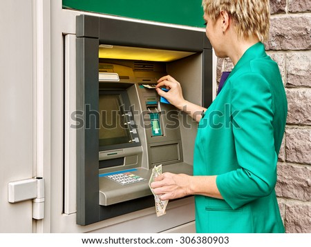Business woman operates an ATM on the street