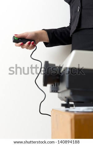 Business woman operating a slide projector against a white wall