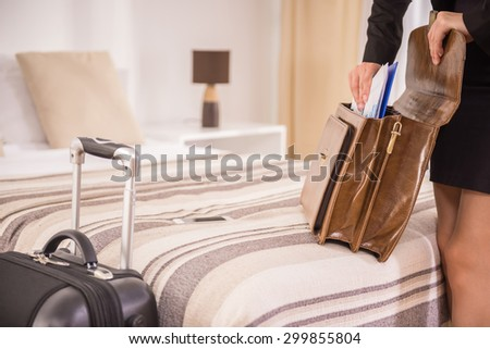 Business woman packing his things into the briefcase on the bed at the hotel room. Close-up. - stock photo
