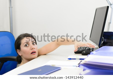 Business woman peeking over the desk - stock photo