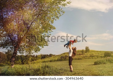 Business Woman Playing with Her Son, Throws Baby on Blue Sky Background Outdoor - stock photo
