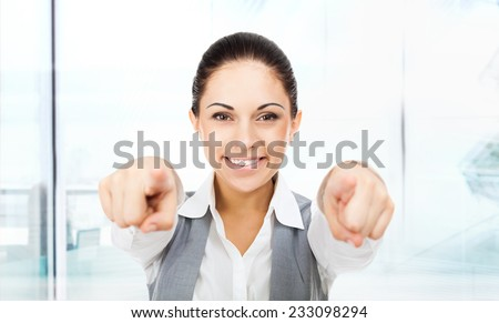 Business woman point finger at you looking at camera. businesswoman excited smile in modern office