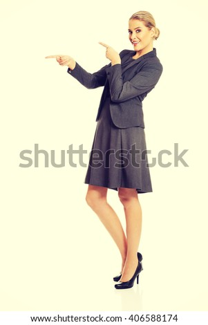 Business woman pointing at copyspace on the left - stock photo