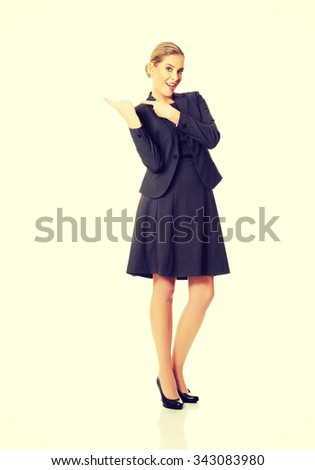 Business woman pointing at copyspace on the right. - stock photo
