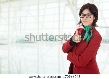 business woman portrait going thumb up, at the office - stock photo
