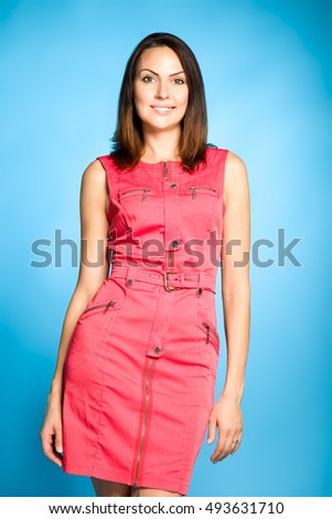 Business woman portrait on blue wall background. Red dress.