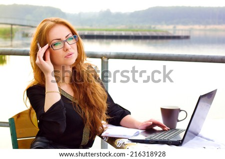 Business woman portrait outdoors with laptop and cup of coffee - stock photo
