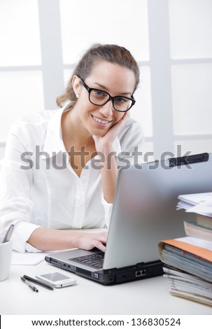 Business woman portrait smiling in an office in front of her laptop