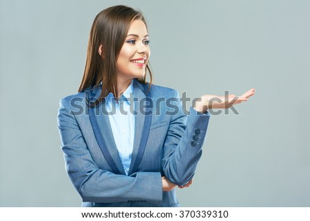 Business woman present you product on hand. Smiling young office worker. - stock photo