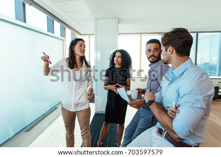 business woman presenting a business plan to her colleagues in boardroom men and woman entrepreneurs