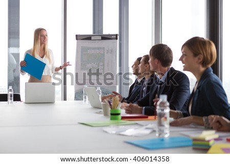Business woman presenting project to her colleagues in modern office. - stock photo