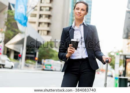 Business woman pulling suitcase walking in city