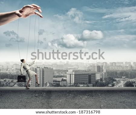business woman puppet walks on the concrete parapet - stock photo