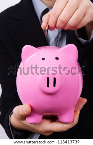 Business woman putting coin into pink piggy bank.