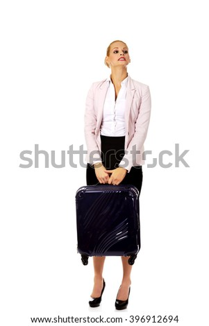 Business woman raising her suitcase - stock photo