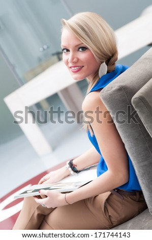 Business woman reading magazine in modern office.