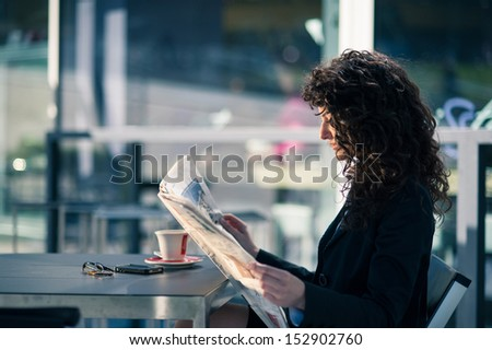 Business woman reading newspaper outdoors sit in a bar. Shallow depth of field.  - stock photo