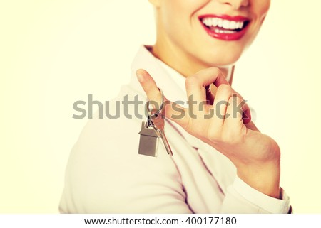 Business woman real estate agent holding keys - stock photo