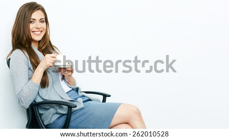 Business woman relaxed with coffee cup sitting in office chair. Isolated portrait. - stock photo