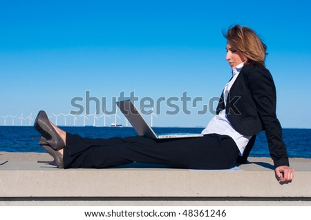 business woman relaxing with laptop on the beach on sunny day