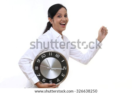 Business woman running and holding a clock against white background - stock photo