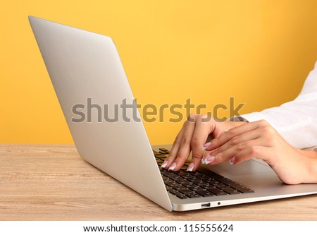 business woman's hands typing on laptop computer, on yellow background close-up