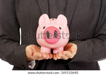 Business woman saving money in piggybank. - stock photo