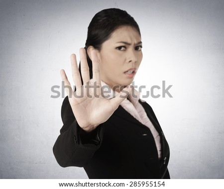Business woman say no, with grunge wall background - stock photo