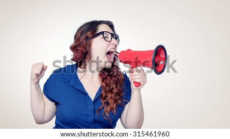 Business woman screaming into a megaphone - stock photo