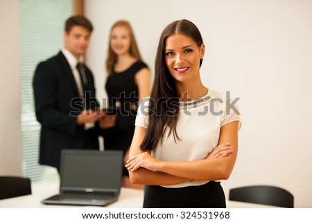 Business woman - secretary  standing in first plain with coworkers in background  Young boss entrepreneur - stock photo