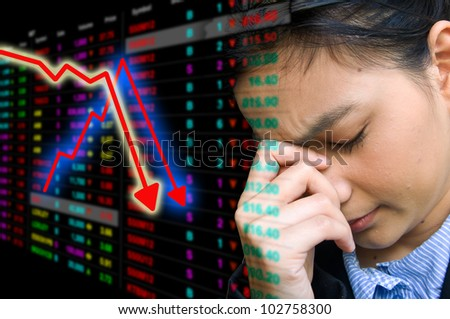 Business woman serious a falling down graph of stock market - stock photo