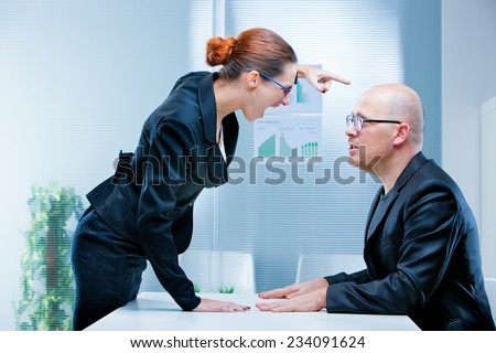 business woman shouting against a business man or a male office worker - stock photo