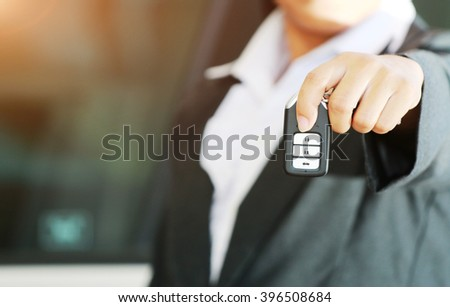 Business woman show a remote car key and operate. car background. - stock photo