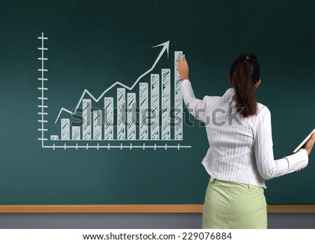 Business woman showing charts on the blackboard  - stock photo