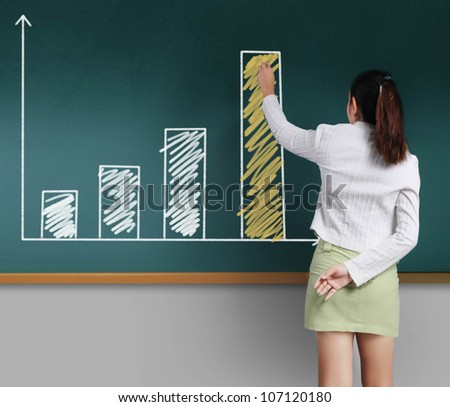 Business woman showing Graph on the blackboard - stock photo
