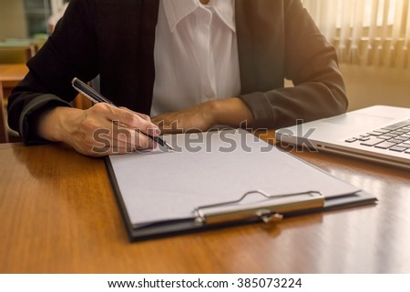 Business woman signing a contract.Vintage tone Retro filter effect,soft focus,low light.(selective focus) - stock photo