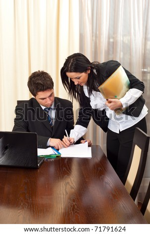 Business woman signing an agreement for other business man partner in a meeting room - stock photo