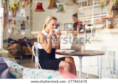Business woman sitting at a table in small coffee shop - stock photo