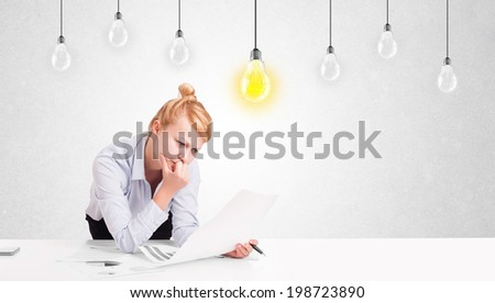 Business woman sitting at table with bright idea light bulbs - stock photo