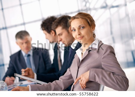 Business woman sitting at the business meeting with her colleagues at the background.