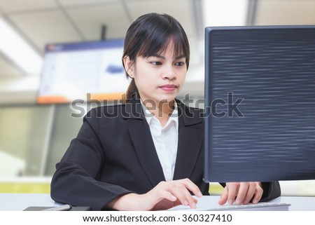 business woman sitting at the counter with a computer available and the status of service to the people. - stock photo