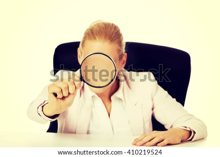 Business woman sitting behind the desk and looking into a magnifying glass - stock photo