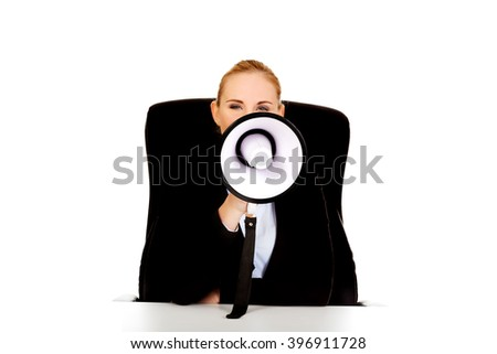 Business woman sitting behind the desk and screaming through a megaphone - stock photo