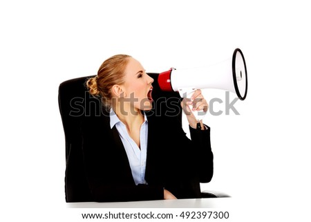 Business woman sitting behind the desk and screaming through a megaphone