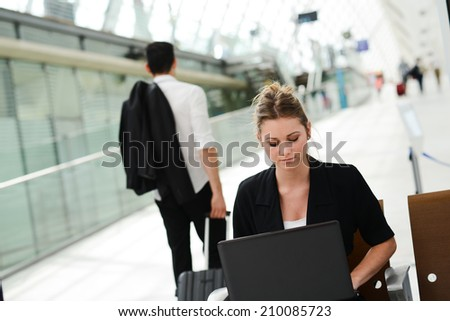business woman sitting in public station and working with a computer in wifi area