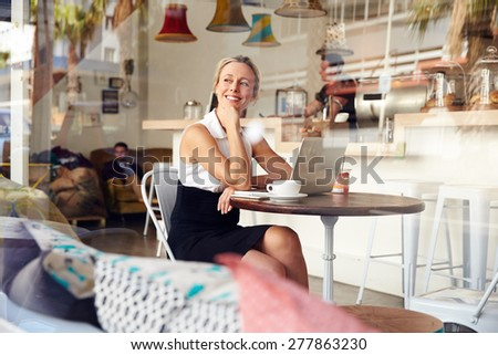 Business woman sitting in small coffee shop - stock photo