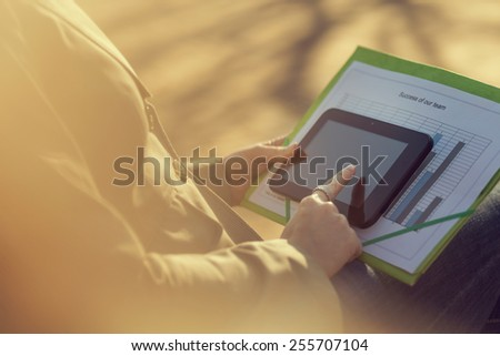 Business woman sitting on a bench in a park, working on a break - stock photo