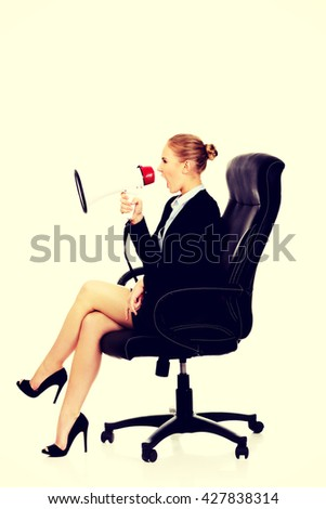 Business woman sitting on armchair and screaming through a megaphone - stock photo