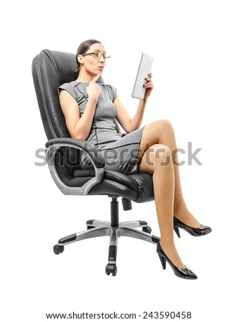 Business woman sitting on chair working with a tablet, isolated over white background - stock photo